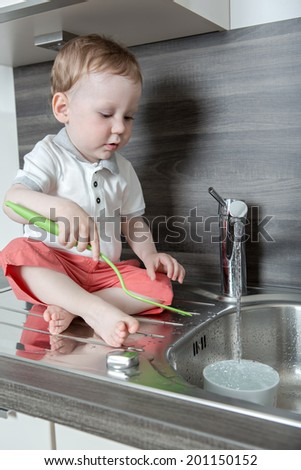 a 1,5 years old boy playing in the kitchen