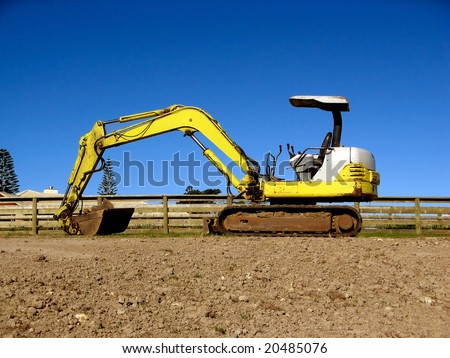 A yellow and white mini digger excavator.  Space for Copy. - stock photo
