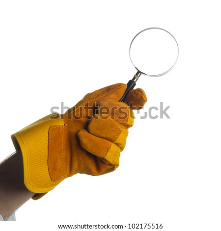 A yellow/brown gauntlet holding a magnifying glass - stock photo