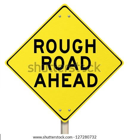 A yellow diamond-shaped road sign cautions people that rough roads are ahead - stock photo