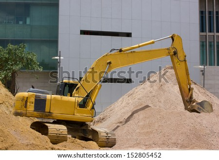 A yellow excavator working on sand. - stock photo