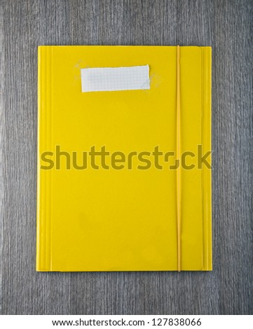 A yellow folder with empty white paper label - stock photo