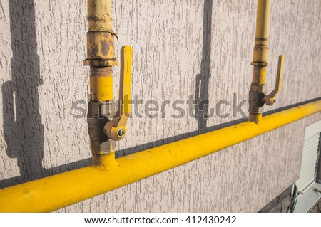 A yellow gas tube, with a tap, outside of a house to canalize the soft energy at home.  - stock photo