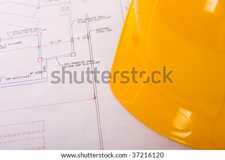 A yellow hard hat lying on top of building plans - stock photo