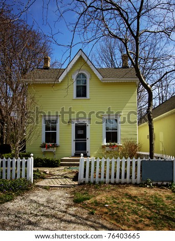 a yellow house with white picket fence - stock photo