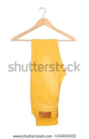 A yellow jeans are on hanger. - stock photo