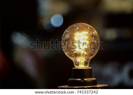 A yellow light bulb lighting in the room with bokeh light and dark background