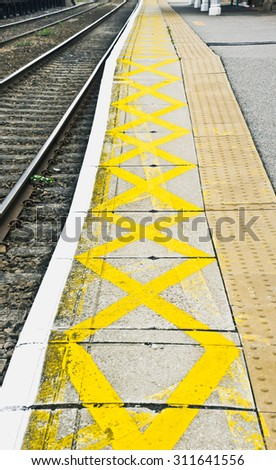 A yellow pattern at the edge of a railway platform to warn of the railway lines - stock photo