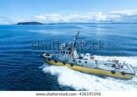 A yellow pilot boat cutting through deep blue water - stock photo