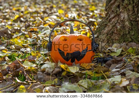 A yellow pumpkin listening to music under the tree