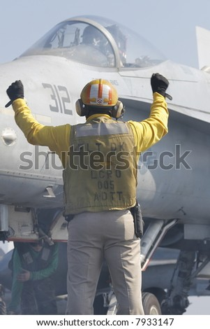 "A ""Yellow Shirt"" Aircraft Director Loads an F/A-18C Hornet onto a Catapult on the Nuclear Aircraft Carrier, USS Enterprise - stock photo"