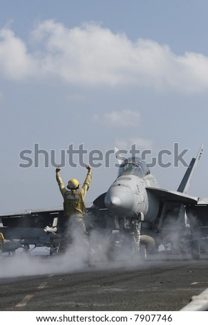 "A ""Yellow Shirt"" Aircraft Director Taxis an F/A-18F Super Hornet onto a Catapult Aboard the Nuclear Aircraft Carrier, USS Enterprise - stock photo"