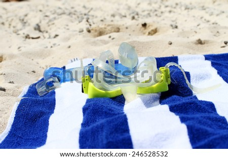 A yellow snorkel placed on a blue and white towel on the beach, asking the question are you ready for your holiday - stock photo