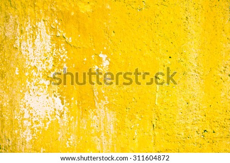 A yellow stone wall which is weathered - stock photo