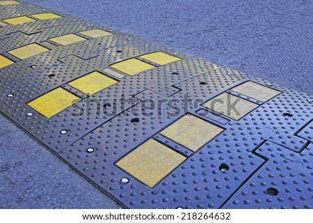 A yellow stripe speed ramp on an asphalt road. - stock photo