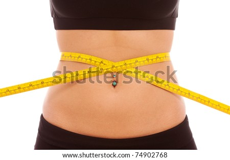 A yellow tape measure around a young females waist - stock photo