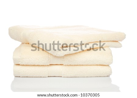 A yellow towels stacked reflected on white background - stock photo