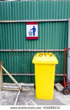 A yellow trash bin with trash sign on green galvanized iron - stock photo