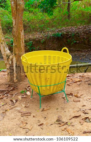 A yellow trash is in the garden. - stock photo
