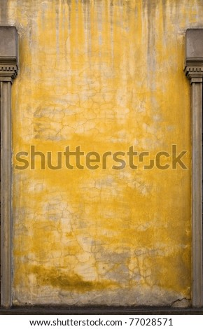A yellow wall on an old building in Italy.  There are interesting variations in the paint and stonework, and posts from large windows on the sides.  Lots of room for copy. - stock photo