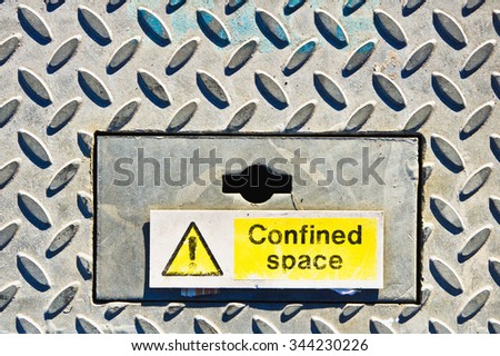 A yellow warning sign on a metal surface indicating a confined space - stock photo