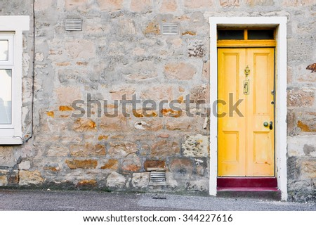 A yellow wooden front door in a stone cottage in Scotland