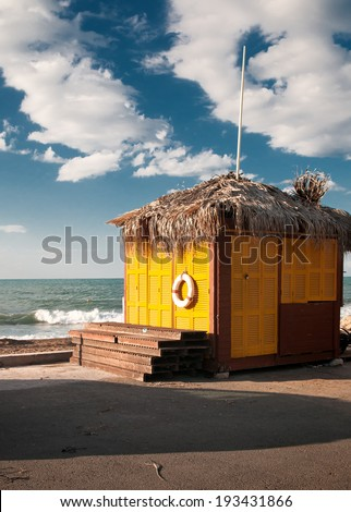 A yellow wooden house and sea .