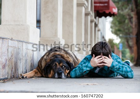 A 10 yeqr old boy and his dog lying down on the sidewalk playing hide and seek - stock photo