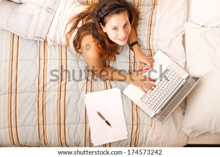 A young adult girl studying on the bed with a Laptop. - stock photo