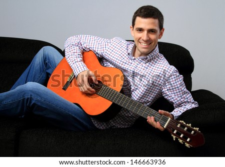 A young adult happy with guitar, on the couch / On the couch with guitar
