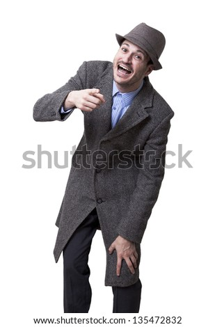 A young adult male wearing an overcoat and a matching hat, looking and pointing at the camera bursting with laughter. Isolated on white background.