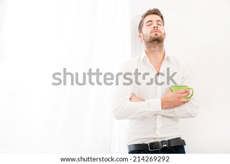 A young adult man at home drinking coffee.  - stock photo