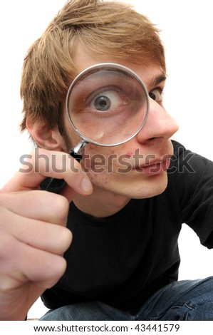 A young adult man looking down  with a magnifying glass up to his eye, searching for just the right clue to crack the case of the mystery. - stock photo