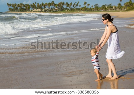 A young adult mother bringing her son for the first time on the beach