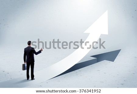 A young adult salesman standing in front of a big arrow pointing up with a shadow in grey empty space concept - stock photo