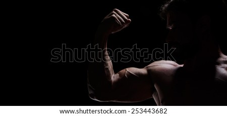 A young adult strong man looking up - stock photo