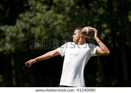 A young adult throwing a football outside. - stock photo