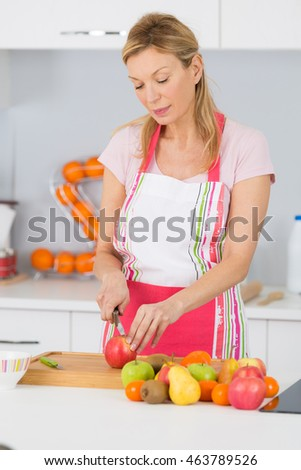 a young adult woman cutting apple in the kitchen