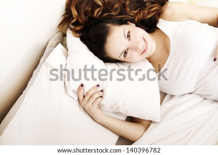A young adult Woman relaxing on the Bed. - stock photo