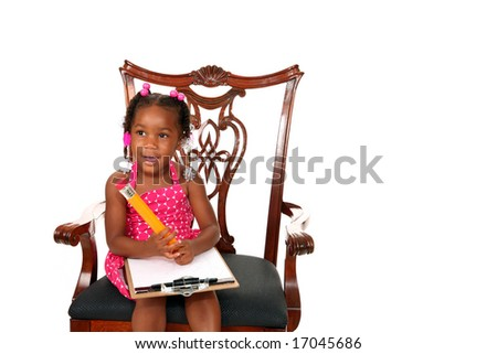 a young african american baby girl draws on paper with a giant pencile
