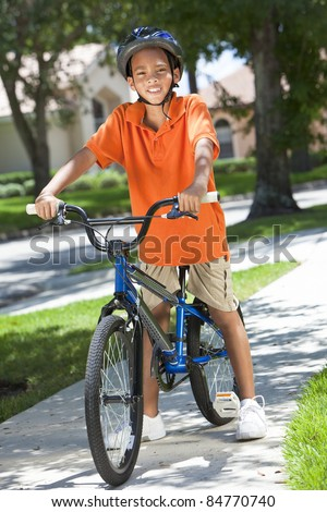 A young African American boy child riding bicycle or bike in the summer - stock photo