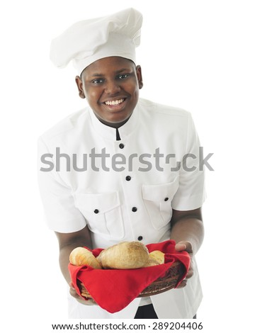 A young African American chef offering the viewer a choice of breads he's made.  On a white background.