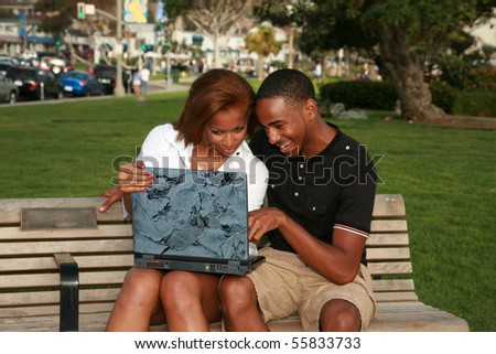 a young african american couple enjoy using a laptop computer outside - stock photo