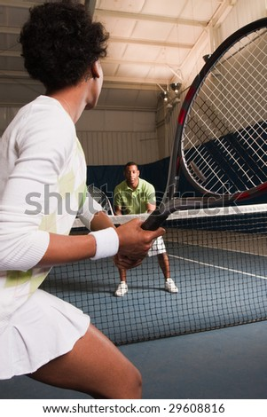 a young african american couple plays tennis - stock photo