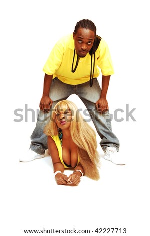 A young African American couple, she is lying on the floor and he standing over her in the studio for white background. - stock photo