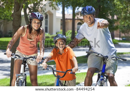 A young African American family, woman, man, father, mother & boy child riding bicycles in the summer