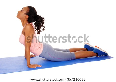 A young African American girl lying on a yoga mat, stretching her body, 
