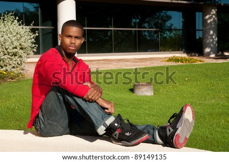a young African-American man sitting outdoors in casual attire
