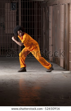 A young african american man with an afro is looking behind him as he is making an escape from a prison cell. Vertical shot. - stock photo