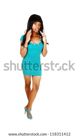 A young African American slim woman standing for white background with her necklace in her mouth and in a short turquoise dress in the studio. - stock photo